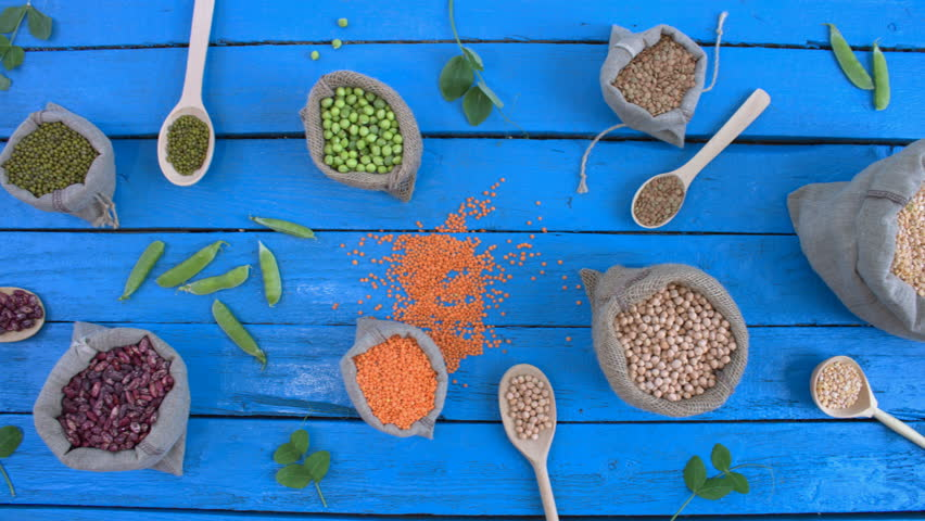 Legumes on wooden ecological background. Beans are located in unusual form on blue wooden table. Bean cultures in woven bags. Camera moves from right to left.  | Shutterstock HD Video #1022202262