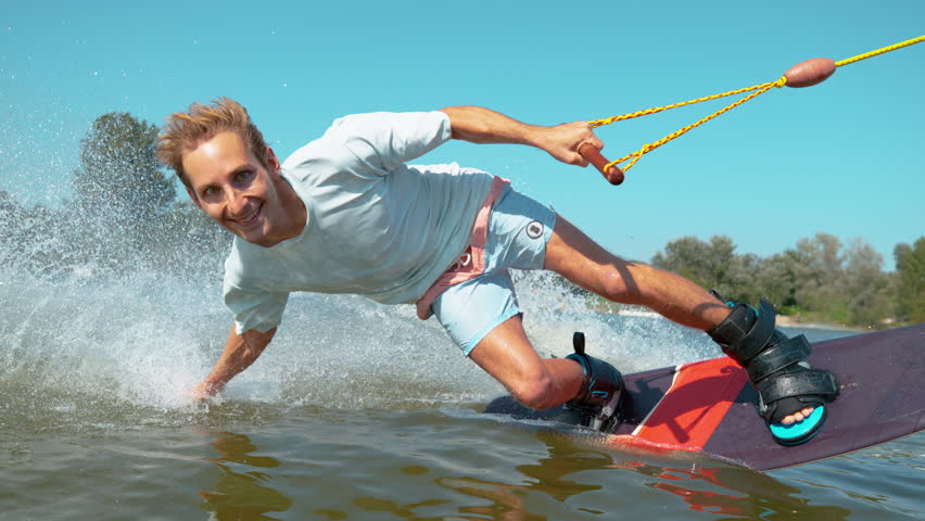 SLOW MOTION CLOSE UP Cheerful young surfer wakeboarding, sliding his hand on water surface, splashing water at camera. Smiling wakesurfer riding waterski cable park on sunny day. Wakesurfing in summer | Shutterstock HD Video #1022227702