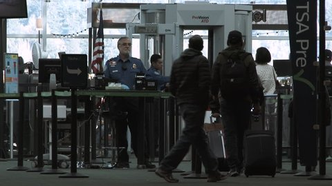 PORTLAND, OREGON / USA - JANUARY 2019: TSA officer checks passenger tickets and identification at security check point in airport.