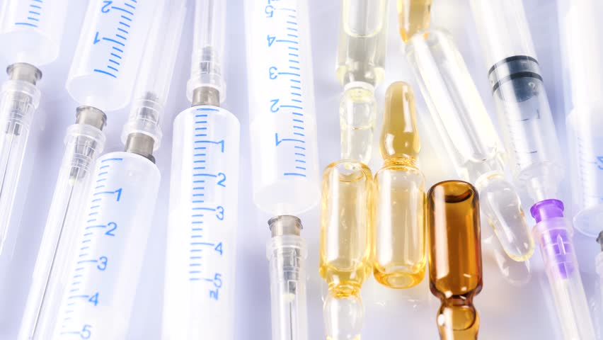 Medical syringes and vials for injection rotate on the table on a white background | Shutterstock HD Video #1022407672