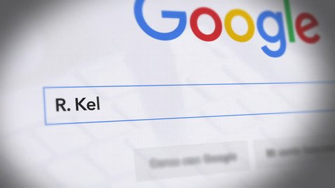 USA-Popular searches in 2019 Google Search Engine - Search For R. Kelly - Monitor with reflection hands typing a search on google