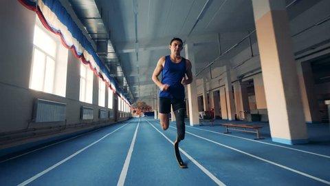 Sportsman runs, wearing prosthesis, close up.