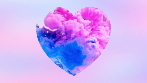 Abstaract colorful ink drops in the water in slow motion mixing in Love shape heart. Blue and Pink ink paint drops swirling and mixing underwater. Colorful Ink Cloud collision isolated with alpha.