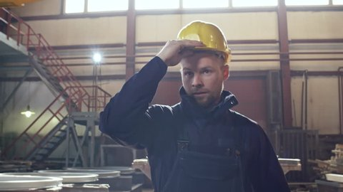 Dolly shot of tired worker in overalls walking through metal fabrication facility of steel plant and putting on hard hat and gloves