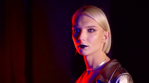 transexual woman with blonde hair and fashion make-up in dark room with colored lights