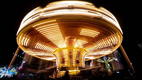 Merry-go-round carousel at night. Amusement park carousel with beautifully painted wooden horses.