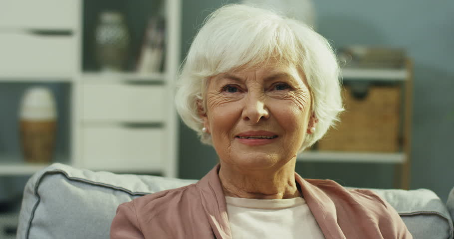 Close up of the old lady on retirement smiling to the camera while sitting on the gray couch in the living room. Portrait. | Shutterstock HD Video #1022506312