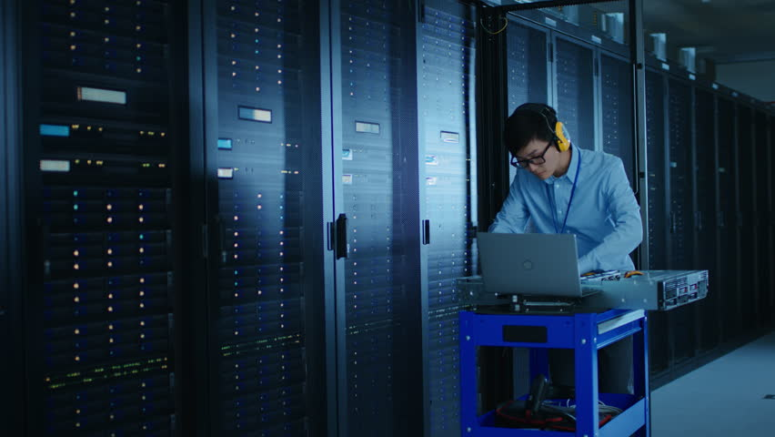 In the Modern Data Center: IT Technician Wearing Protective Headphones Working with Server Racks, on a Pushcart Installing New Hardware. Engineer Doing Maintenance and Diagnostics of the Database. | Shutterstock HD Video #1022552572