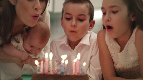 Happy family birthday party at home. Family blowing candle flames on party cake together. Close up of mother with children blowing candles on birthday cake in slow motion