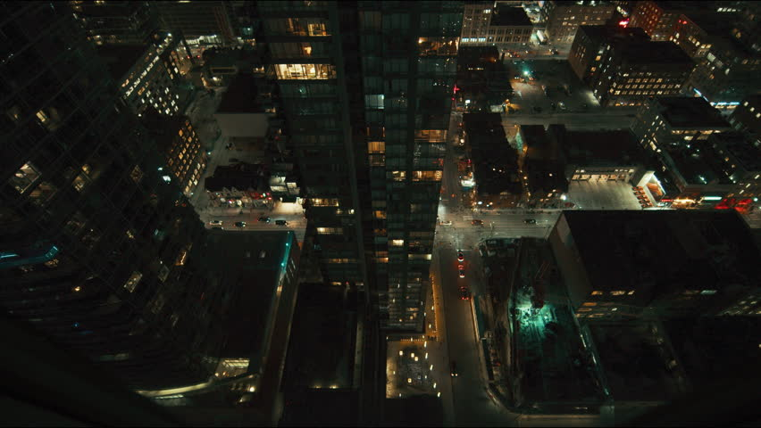 Wide angle down shot of city skyscraper at night with lights on. Dark and moody with an epic feeling. Downtown big office buildings in a major city. Cars drive by with their lights on.  | Shutterstock HD Video #1022580172