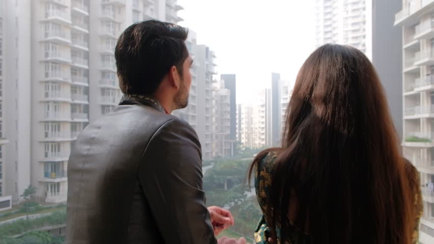 Handheld shot of a lovely couple in sun admiring the view from their expensive brand new penthouse apartment with a view to the suburban metropolis  | Shutterstock HD Video #1022584252