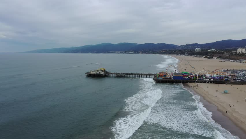 Arial view of Santa Monica pier in Los Angeles, California on an overcast day with the city and coastline in the background   Shutterstock HD Video #1022586502