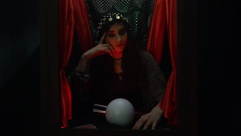Young fortune teller woman sitting in a small booth