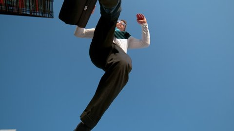 SLOW MOTION, BOTTOM UP: Cheerful young businessman jumps over the camera after getting promoted. Happy young Caucasian man carrying a briefcase jumping in the air after work on a sunny spring day.