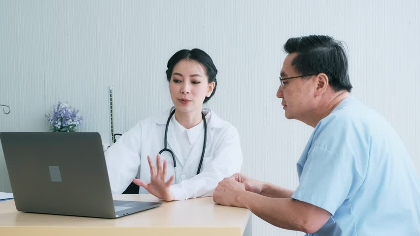 Doctor with patient. Young female medical doctor talking to a senior patient at hospital. Looking at her laptop to discuss medical examination result. Senior care medical and insurance concept. | Shutterstock HD Video #1022636872