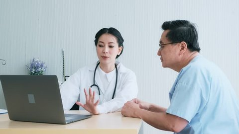 Doctor with patient. Young female medical doctor talking to a senior patient at hospital. Looking at her laptop to discuss medical examination result. Senior care medical and insurance concept.