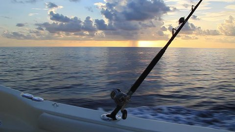 Handheld shot oning boat. Deep sea fishing boat running at sunset with rain cloud in distance. Fishing rod and reel in shot. Space for copy text.