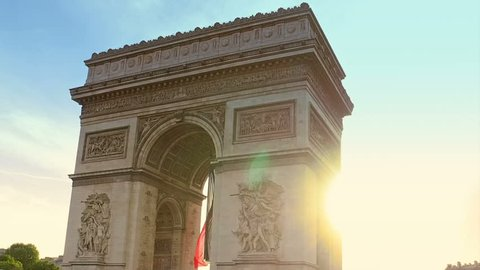 Hyperlapse at sunset around the Arc de Triomphe with tourists. Arch of triumph at the western end of the Champs Elysees and at the center of Place Charles de Gaulle