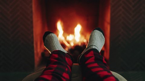 Relaxation. Someone puts their feet up on a foot rest by the fire. They're wearing cozy socks, and plaid pants. It's incredibly cozy.