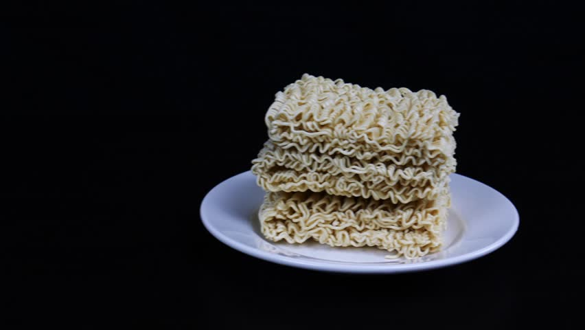 Instant noodles in a plate on a black background. Fast food, junk food, unhealthy food. Rolton. Doshirak | Shutterstock HD Video #1022690902