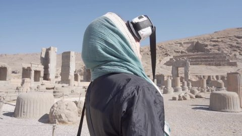 Female tourist enjoying 3d reconstruction of persepolis through vr virtual  reality headset, iran  amazing ruins of the ceremonial capital of the  achaemenid empire  ancient persian city