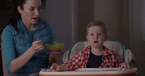 Mother Feeding her Child Boy with Porridge for Breakfast and Baby Eating Food. Shot on Red Camera