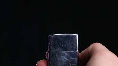 Zippo lighter being lit on a black background