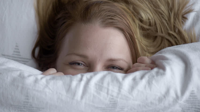 Closeup of Lovely young Woman Lies in Bed Covered with Blanket. Top view of Girl is Shy and Cover of her Face with Blanket. Female Smiling and Looking at Camera.