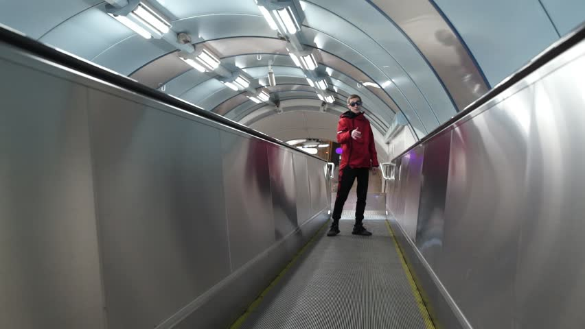 Handsome slim active short-haired guy wearing sunglasses and red sportive jacket with hood is emotionally rapping and looking at camera standing at moving travelotar at some metro station.
