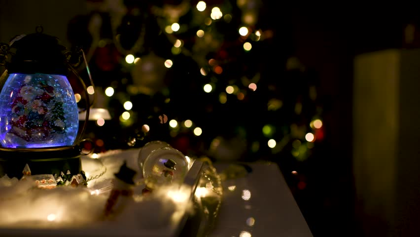 Cute Christmas decoration with snow globes on the table and lights on and off with a blurred Christmas tree in the background. Panoramic plane