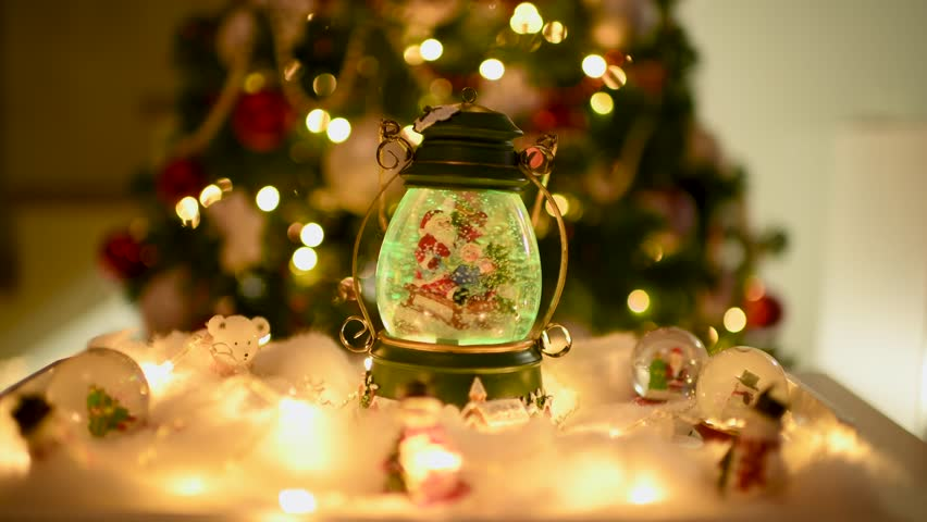 Beautiful Christmas decoration with snow globes on the table and lights on and off with a blurred Christmas tree in the background. Flat plane