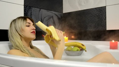 An attractive woman sits in the bathroom and brushes the big yellow banana and starts with the pleasure of eating it. The hungry girl eats a yellow banana quickly in the bathroom