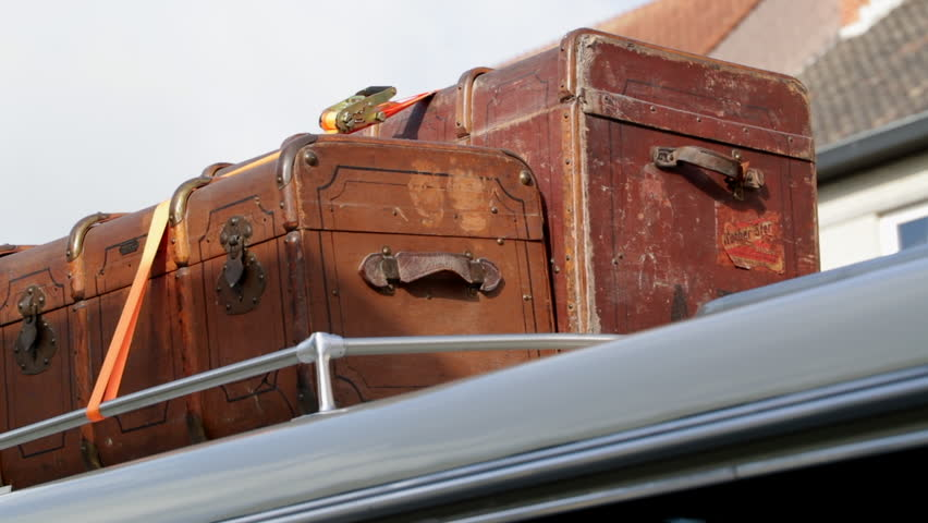 2 old vintage suitcases fastened together on top of an oldtimer bus coach.