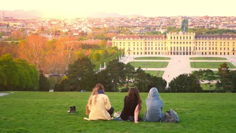 VIENNA, AUSTRIA - CIRCA APRIL 2018: Panorama view on the Schoenbrunn Palace as tourist pass by on the walkway of the castle park circa April 2018 in Vienna, Austria.