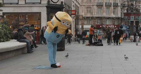 LONDON ENGLAND JANUARY 2019: Street performer dancer singer minion costume silly funny weird circus clown square