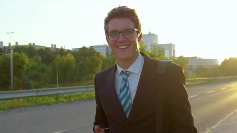 SUPER SLOW MOTION, SUN FLARE, PORTRAIT: Smiling Caucasian yuppie walking down the sunny sidewalk with his cell phone in hand. Cheerful young businessman texting and walking home after a successful day