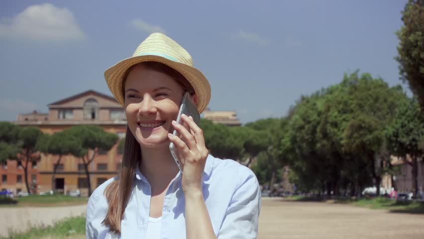 Young woman walking on Circus Maximus and using mobile phone in slow motion in Rome, Italy. Happy female traveler enjoying vacation in european city. Smiling girl chatting with friend via cellphone | Shutterstock HD Video #1022835982