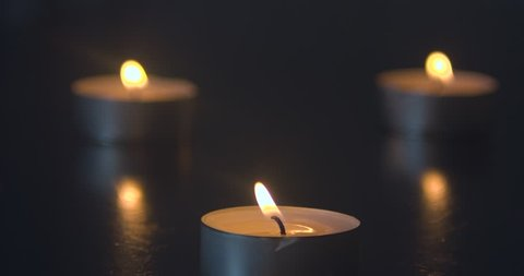 Three Candles Burning on a Black Table