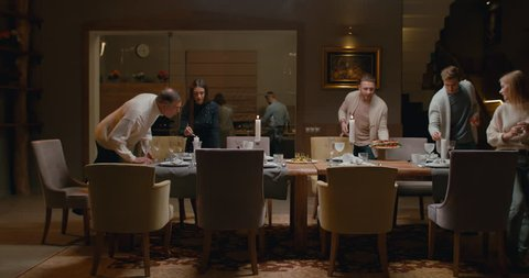 WS Large family or group of friends setting the table, preparing for a dinner. 4K UHD 60 FPS SLOW MOTION Blackmagic RAW