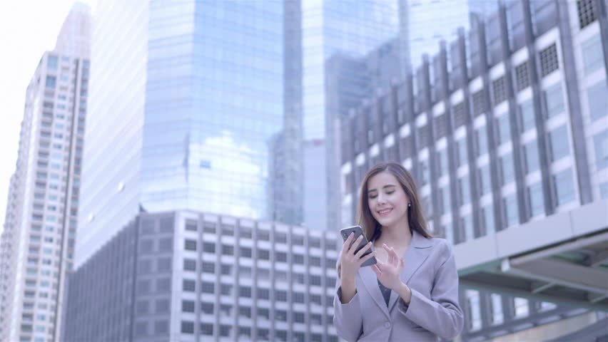 Young caucasian businesswoman Using Smart Phone are walking in city centre Thailand.  communication, everyday life Technology Concept. SLOW MOTION | Shutterstock HD Video #1022861902