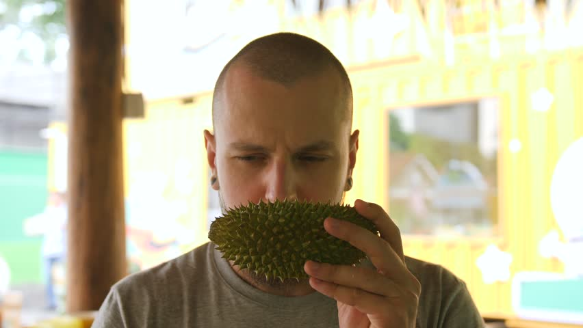 Young Bearded Man Trying Durian First Time and Do not Like the Smell. 4K Slowmotion. Kuala Lumpur, Malaysia.
