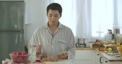 Attractive young asian gay couple having breakfast in kitchen. Man cooking breakfast for him boyfriend with attractive smiling. People with gay, homosexual, relationship concept.