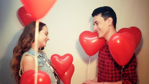 Man makes present to his lovely sweetheart girl. Lover's valentine day. Valentine Couple. Boy gives to his girlfriend jewelry. Wedding ring. Propose background red balloons hearts. Happy smile girl.