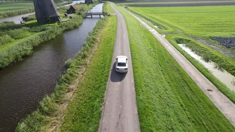 Car driving over dike followed by drone.