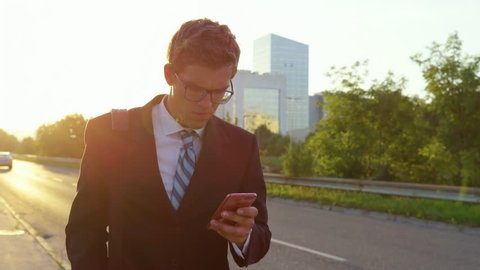 SLOW MOTION CLOSE UP SUN FLARE: Stressed yuppie looks around the city as he walks home at sunset and receives bad news over his phone. Young businessman gets anxious after reading some worrisome news.