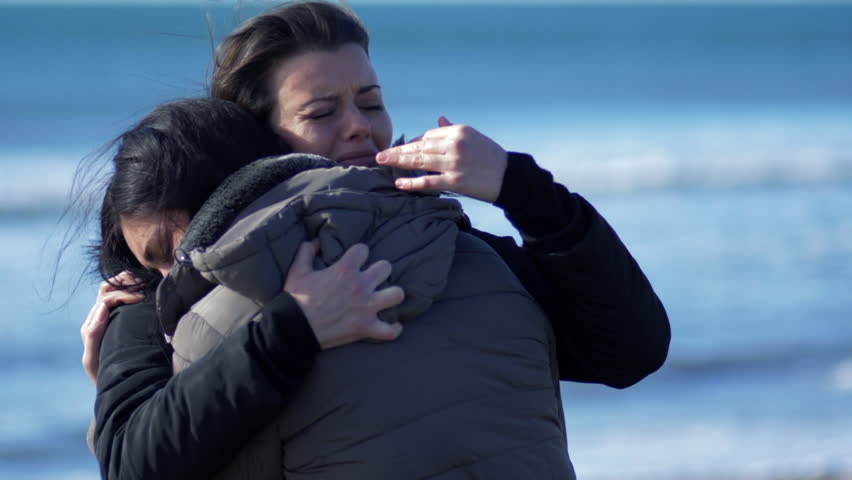 Two women crying hugging each other in winter in front of the ocean super slow motion