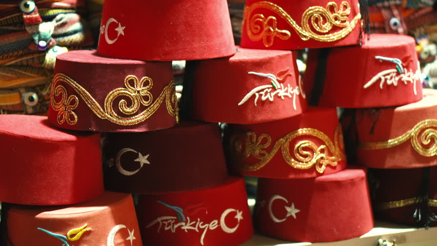 The headdress of the Turkish red Fes is sold on the counter of the market in Turkey. Traditional clothes. Souvenirs and gifts from a tourist trip. Eastern culture