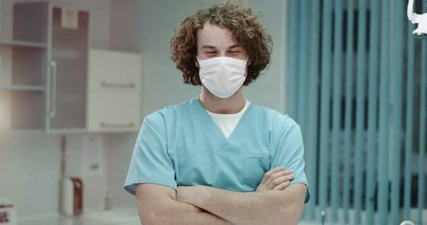 Young dentist man or doctor in the hospital closeup looking straight to the camera and take off the surgical mask and happy smiling large , he have a perfect white teeth and charismatic face.