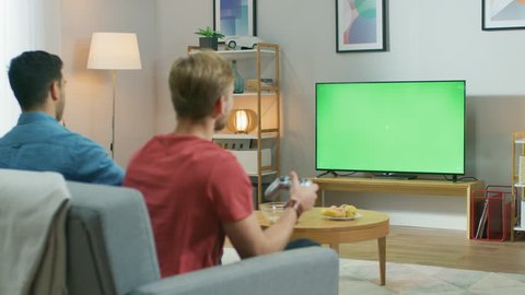 In the Living Room Two Friends Sitting on a Couch Holding Controllers Playing Competitive Video Game on a Green Chroma Key TV Screen. One Friend Teaser Another for Losing.