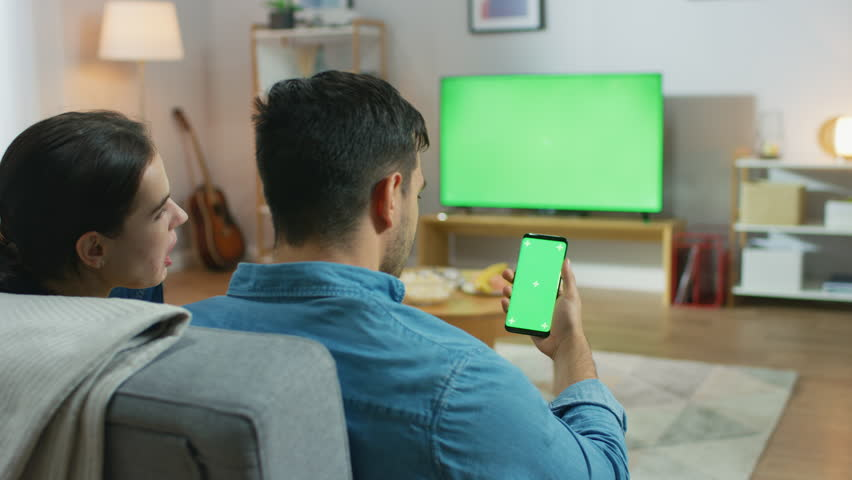 Happy Couple Sitting At Home in the Living Room Watching Green Chroma Key Screen Television, Relaxing on a Couch. Guy also Uses Green Mock-up Screen Smartphone. | Shutterstock HD Video #1022993092